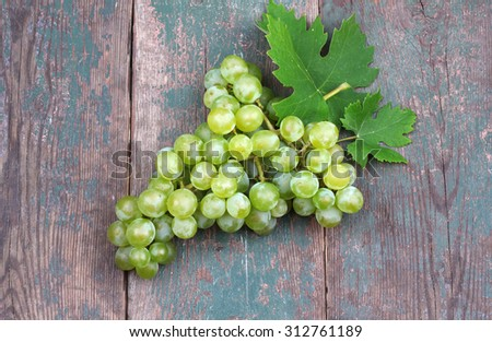 Green and purple round grapes on old wooden table