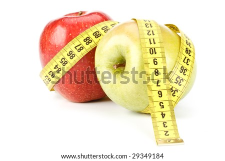 Green and red apples with measuring tape.
