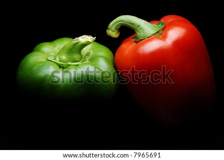 Green and red bell peppers with dramatic lighting on black background - stock photo