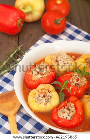 Green and red bell stuffed peppers in tomato sauce