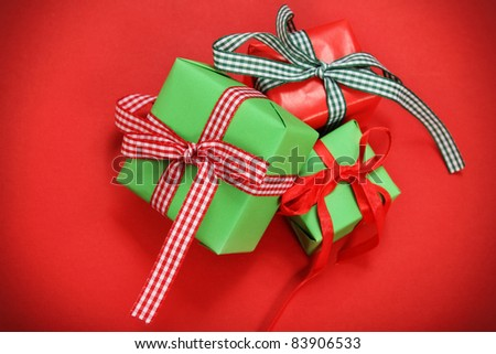 Green and red christmas presents over red background