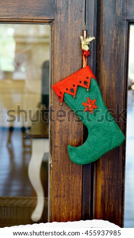 Green and red christmas sock with snowflakes for Santa gifts hanging on wooden door or window. Holidays symbol stocking