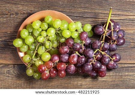 Green and red grapes in plate on old wooden table, top view