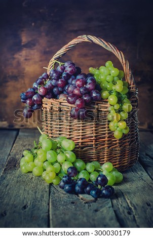 Green and Red Grapes in Rural Basket on Wooden Background. Country style - stock photo