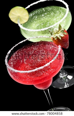 Green and Red Margarita in front of a black background with fresh garnish - stock photo