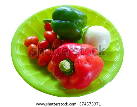 green and red pepper in green dish isolated on whith background. - stock photo