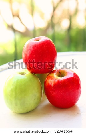 green and red raw apples on white table - stock photo