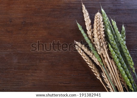 green and ripe wheat on a wooden background