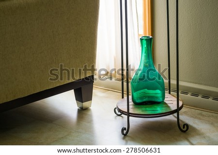 Green and turquoise vase sits on plant stand - stock photo