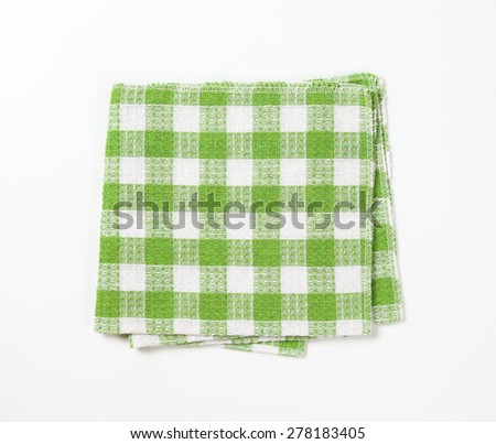 green and white checkered dishtowel on white background