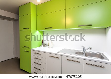 Green and white furniture in a modern kitchen interior - stock photo