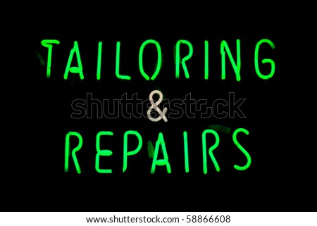 Green and white neon sign of the words 'Tailoring & repairs' on a black background.