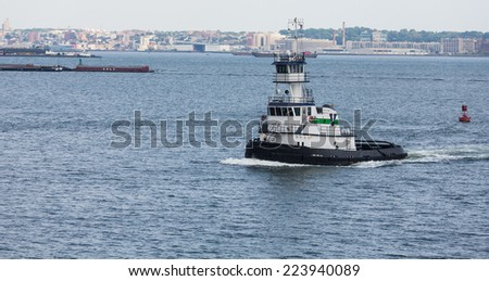 Green and white tugboat from Brooklyn with city in background - stock photo