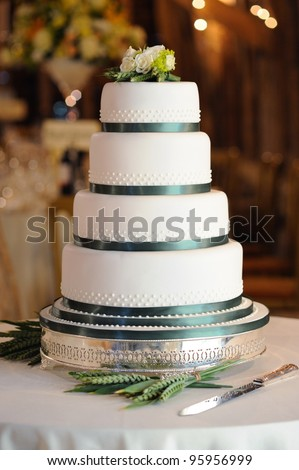 Green and white wedding cake at reception in barn.