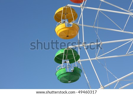 green and yellow cabins of Ferris wheel in St-Petersburg - stock photo