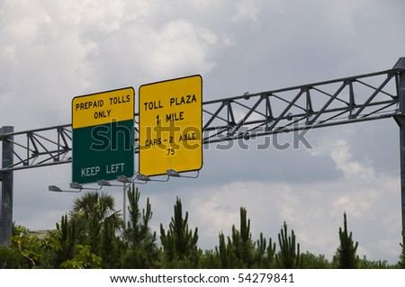 Green and yellow interstate toll plaza sign on a stormy day - stock photo