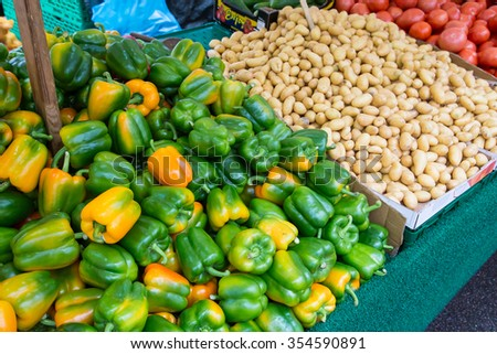 Green and yellow peeper with potatoes on street market - stock photo