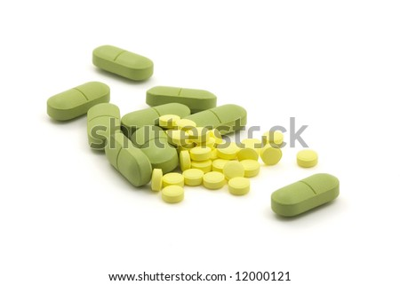 Green and yellow pills with dose on white background - stock photo