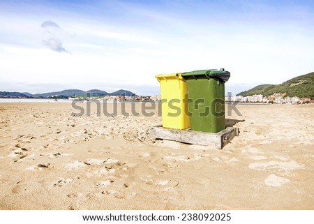 Green and yellow plastic roller bins in the beach. - stock photo