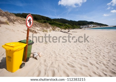 Green and yellow plastic roller bins on a clean Spanish beach with dunes and a calm bay in the distance. Bares, Galicia. - stock photo