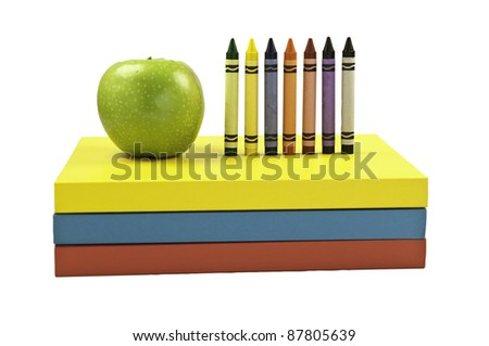 Green apple along side colored crayon on top of three books. This has a clipping path. - stock photo