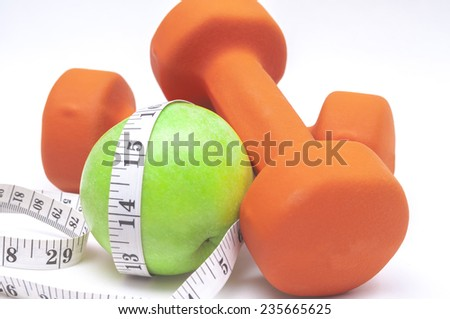 Green apple and a dumbbell on white background  - stock photo