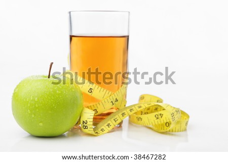 Green apple and a glass of juice with measuring tape for diet and healthy life concept with lots of copy space