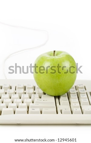 green apple and computer keyboard, concept of online learning - stock photo