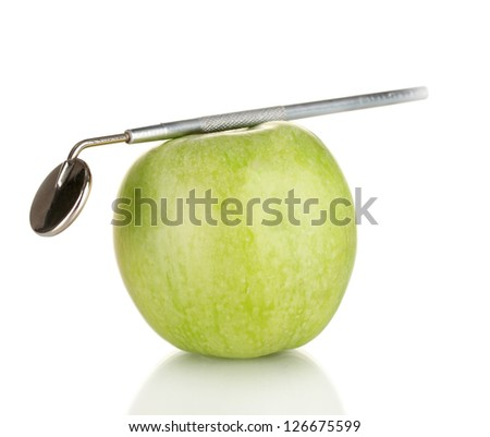 Green apple and dental tool isolated on white - stock photo