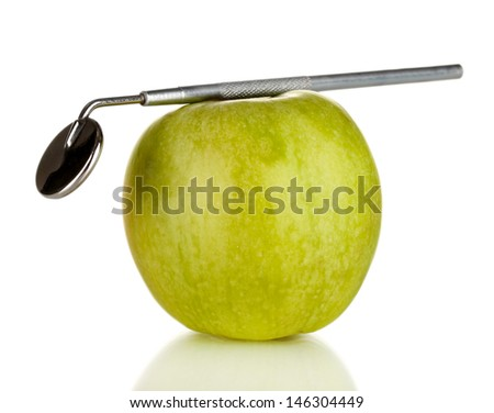 Green apple and dental tool isolated on white