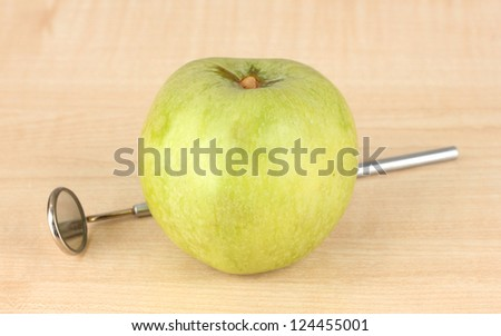 Green apple and dental tool on wooden background