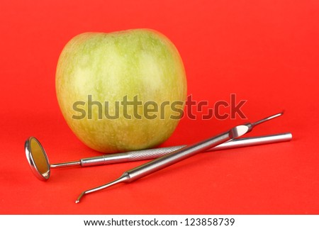 Green apple and dental tools on color background - stock photo