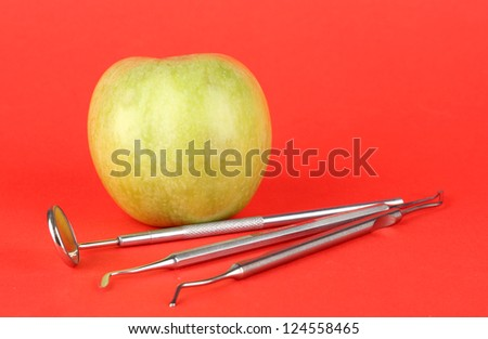 Green apple and dental tools on color background