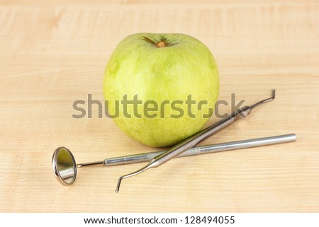 Green apple and dental tools on wooden background