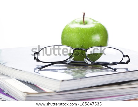 green apple and glasses on magazine and  book stack close up - stock photo
