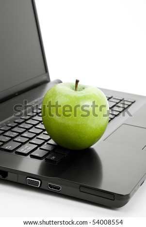 Green apple and laptop close up - stock photo