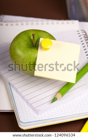 green apple and pencil on empty page of a notebook