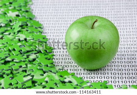 green apple and puzzles on a binary code - stock photo