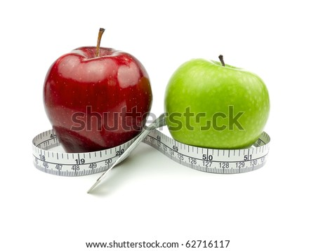 Green Apple and Red Apple with measuring tape on white background - stock photo