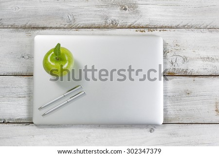 Green apple and silver pens on top of laptop with rustic desktop in background.   - stock photo
