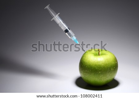 Green apple and syringe over gray gradient