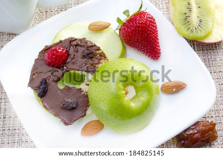 Green apple bagel served on white plate with strawberry