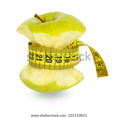 Green apple core and yellow measuring tape isolated on white background - stock photo