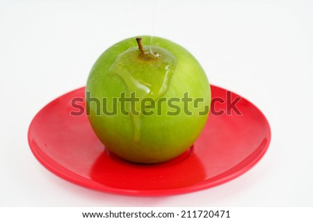 Green apple coverd in honey on Rosh Hashanah Jewish holiday.White background with copy space - stock photo