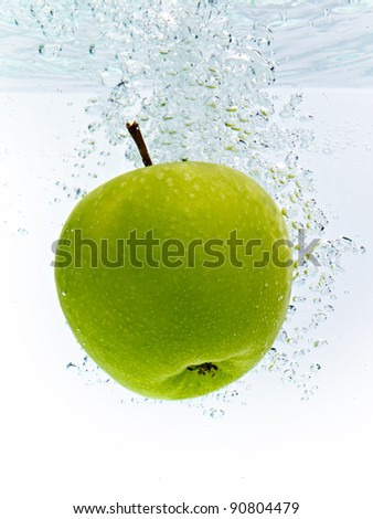 green apple dropped into water - stock photo