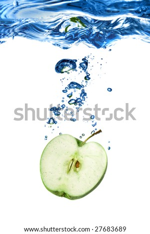 green apple dropped into water with bubbles isolated on white