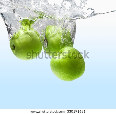 green apple dropping into water  - stock photo
