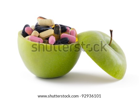 Green apple filed with colourful pills, isolated on white background. - stock photo