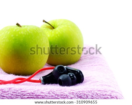 green apple fitness towel and headphones on white background