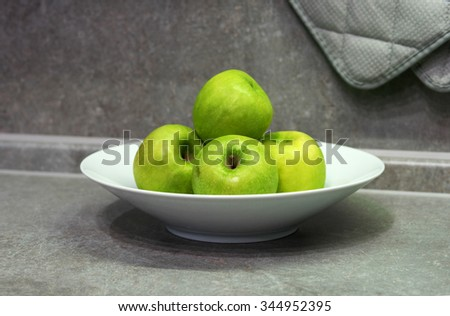 Green apple in a white plate on a gray table top - stock photo